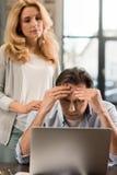 W średnim wieku kobieta patrzeje wzburzonego męża używa laptop w domu Zdjęcia Royalty Free