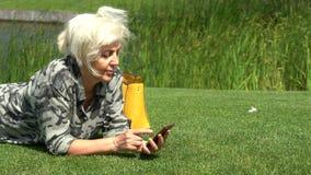 W średnim wieku kobieta relaksuje na trawie obok jeziora zdjęcie wideo