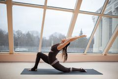 W średnim wieku kobieta robi joga jeźdza Końskiemu ćwiczeniu, anjaneyasana poza na macie przed wielkimi okno , ćwiczenie sprawnoś Obrazy Royalty Free