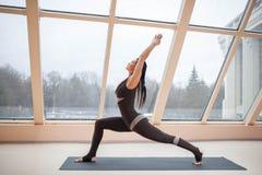 W średnim wieku kobieta robi joga w Virabhadrasana Jeden lub wojownika Jeden joga pozie na macie przed wielkimi okno , ćwiczeń fi Zdjęcia Stock