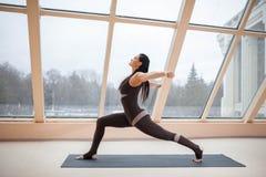 W średnim wieku kobieta robi joga w Virabhadrasana Jeden lub wojownika Jeden joga pozie na macie przed wielkimi okno , ćwiczeń fi Obrazy Royalty Free