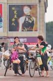 W średnim wieku kobieta ruchliwie z mądrze telefonem na ulicie, Pekin, Chiny Fotografia Stock