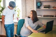 W średnim wieku kobieta sprawdza nastoletniego ` s syna ` s laptop, zakazujący materia Zdjęcia Stock