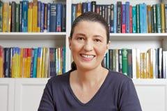 W średnim wieku kobieta uśmiechu książki fotografia stock