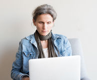W średnim wieku kobieta używa komputer Obraz Royalty Free