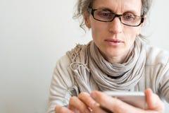 W średnim wieku kobieta z szkłami i mądrze telefonem Zdjęcia Royalty Free