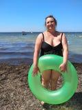 W średnim wieku kobiety pozycja na plaży z nadmuchiwanym okręgiem Obrazy Royalty Free