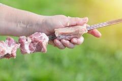 W średnim wieku kobiety ręka stawia kawałki mięso dla shish kebabu grilla na skewer z zielonym rozmytym tłem i słońcem Zdjęcia Royalty Free
