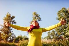 W średnim wieku kobiety uczucie bezpłatny i szczęśliwy na brzeg rzeki na jesień dniu Starszy damy dźwiganie wręcza up obraz royalty free