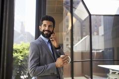 W średnim wieku Latynoski biznesmen używa telefon i trzymający filiżankę Obrazy Royalty Free