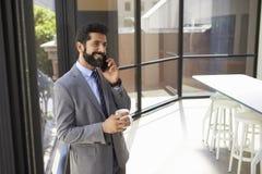W średnim wieku Latynoski biznesmen używa telefon i trzymający filiżankę zdjęcie royalty free
