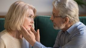 W średnim wieku męża uderzania żony twarz, seansu poparcie i miłość, obraz royalty free