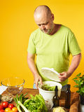 W średnim wieku mężczyzna kucharza świeża sałatka Obraz Stock