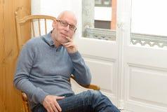 W średnim wieku mężczyzna obsiadanie blisko okno Zdjęcia Royalty Free