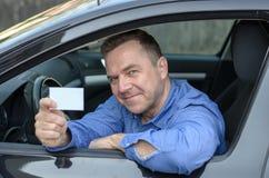 W średnim wieku mężczyzna opiera od samochodu pokazuje jego koncesję Obraz Stock