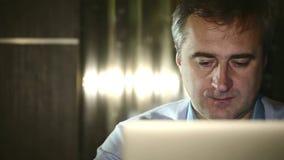 W średnim wieku mężczyzna pracuje przy komputerem w lab zbiory