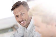 W średnim wieku mężczyzna przy biurem wśród inny Zdjęcie Stock