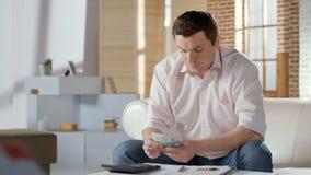W średnim wieku mężczyzny odliczający pieniądze, planujący budżet dla hipoteki i użyteczność zdjęcia stock