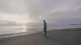 W średnim wieku mężczyzny skarbu myśliwy w hełmofonach z wykrywacz metalu pracuje na oceanu piaska plaży przy zmierzchem zbiory wideo