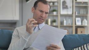 W Średnim Wieku mężczyzny uczucie Niepokojący podczas gdy Czytający dokument, kontrakt zdjęcie wideo