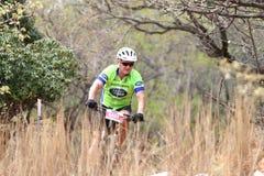 W średnim wieku męska jazda przez krzaka przy rower górski rasą Zdjęcia Royalty Free