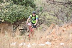 W średnim wieku męska jazda przez krzaka przy rower górski rasą Obraz Royalty Free