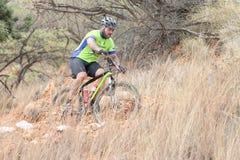 W średnim wieku męska jazda przez krzaka przy rower górski rasą Obrazy Stock