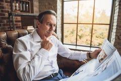 W średnim wieku męska osoba czyta gazetę Obrazy Royalty Free