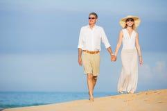 W Średnim Wieku para Cieszy się spacer na plaży Zdjęcia Royalty Free