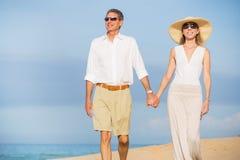 W Średnim Wieku para Cieszy się spacer na plaży Zdjęcie Stock