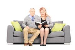 W średnim wieku para czyta książkę sadzał na kanapie Zdjęcia Royalty Free