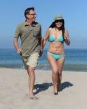 W średnim wieku para na piaskowatej plaży Obraz Royalty Free