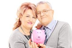 W średnim wieku para trzyma prosiątko banka Zdjęcia Stock