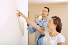 W średnim wieku para wybiera punkt dla dziury w ścianie Fotografia Royalty Free