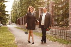 W średnim wieku pary małżeńskiej odprowadzenie w parku w lecie, ślubna rocznica obrazy royalty free