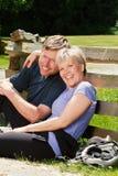 W średnim wieku pary obsiadanie na zewnątrz opierać przeciw ogrodzeniu Fotografia Stock