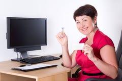 W średnim wieku pośrednik w handlu nieruchomościami obsiadanie w biurze fotografia stock