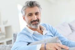W średnim wieku powabny mężczyzna obsiadanie w kanapie Zdjęcia Royalty Free