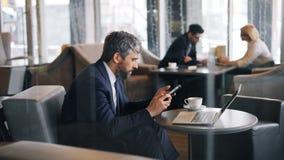 W średnim wieku przedsiębiorca używa smartphone macania ekranu obsiadanie w cukierniany samotnym zbiory