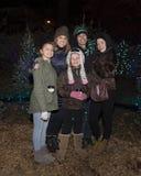 W średnim wieku rodzice i trzy córki na zewnątrz pozyci przed choinkami Zdjęcia Royalty Free