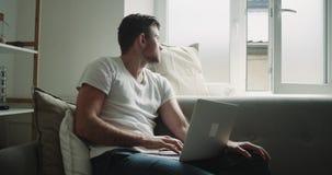 W żywym pokoju w ranku mężczyźnie relaksującego sprawdzał jego laptopu obsiadanie na kanapie zdjęcie wideo