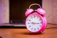Розовые часы на предпосылке компьтер-книжки Начало w стоковое фото rf