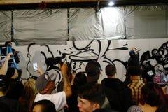Οι άνθρωποι ψεκάζουν την τέχνη χρωμάτων στον τοίχο δεδομένου ότι άλλοι άνθρωποι καταγράφουν τη δραστηριότητα W Στοκ Εικόνες