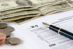 W-9 tax form. W-9 income tax form with pen and american dollars Stock Photos