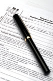 W-9 tax form and a pen Stock Images