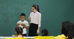 W Angielskiej klasie, Azjatycka chłopiec czyta książkę zdjęcie wideo