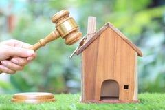W?asno?ci aukcja, kobiety r?ka mienia m?oteczka dom na naturalnym zielonym tle, drewniany i wzorcowy, prawnik domowa nieruchomo?? obraz stock