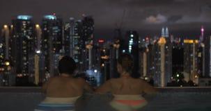 W basenie na dachu hotel w Kuala Lumpur, Malezja mężczyzna z kobietą patrzeje nocy miasto zdjęcie wideo