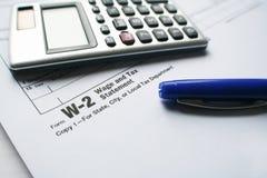 W-2 belastingsvorm met Pen & Hoge Calculator - kwaliteit stock foto