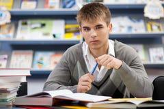 W bibliotece przystojny męski uczeń Zdjęcie Stock
